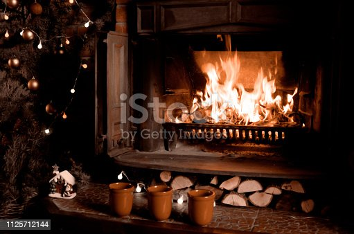 Fireplace with burning fire, three cups and Christmas tree.Warm home interior at night