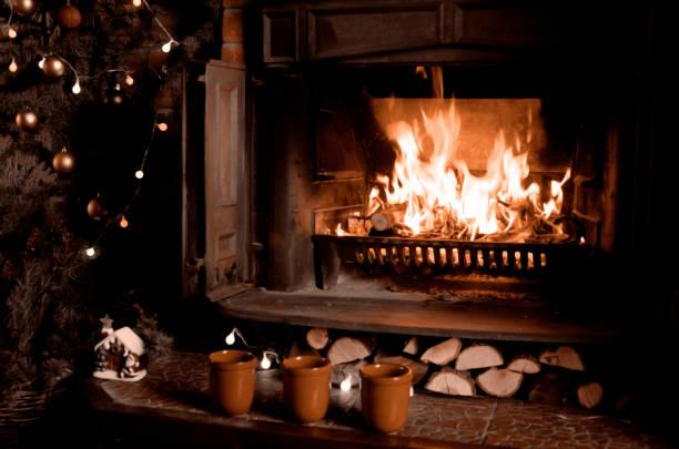 spis med brinnande eld, tre koppar och julgran. varma heminredning på natten - cozy at christmas bildbanksfoton och bilder