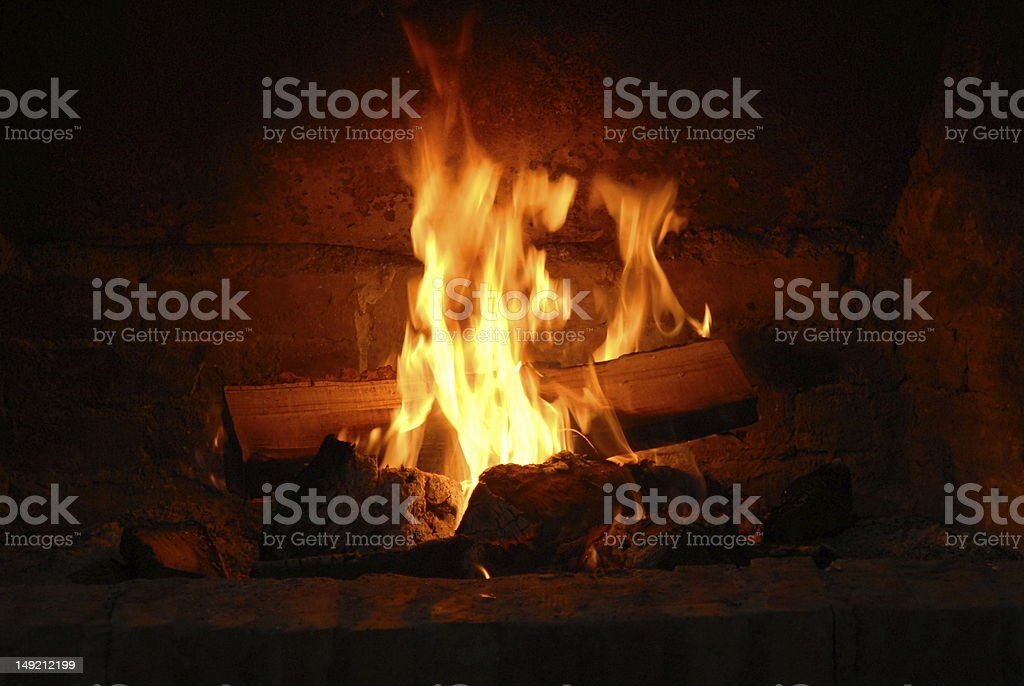 Fireplace with wood on fire giving a warm environment stock photo