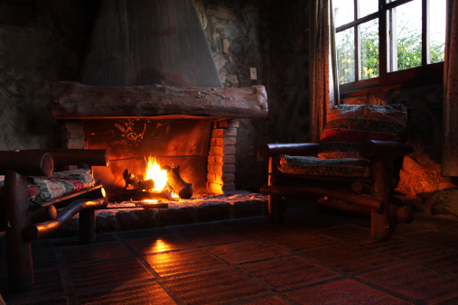 Fireplace with wooden logs, chairs and window