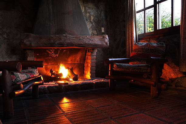 fireplace with wooden logs, chairs and window - fireplace stockfoto's en -beelden
