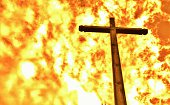 Wooden cross set against a fiery inferno.