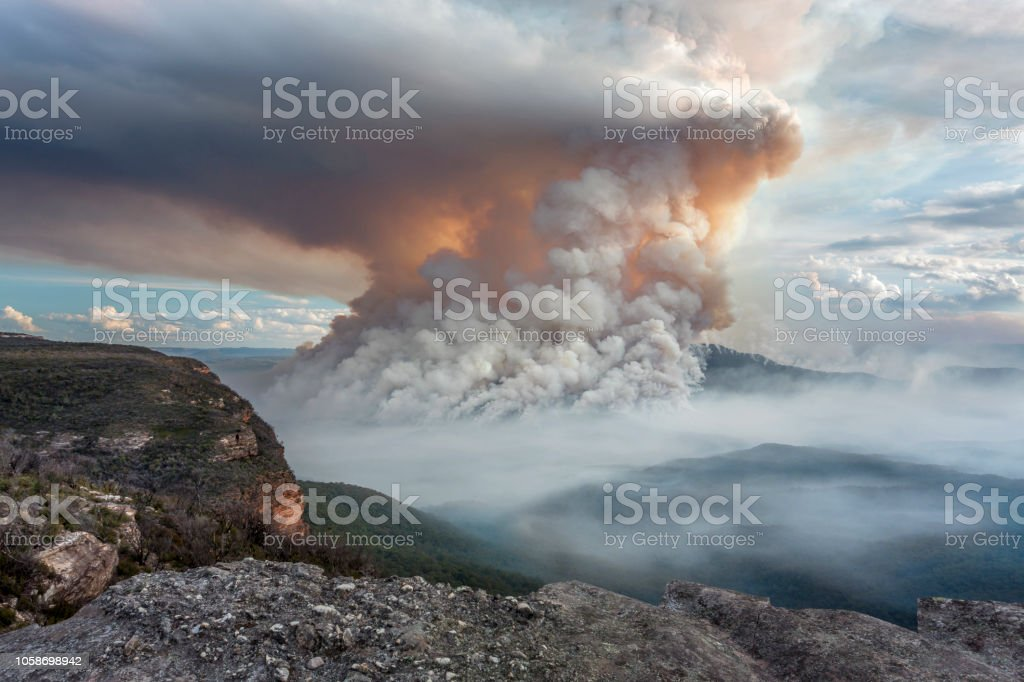 Fires burning on Mount Solitary plumes like volcano Mount Solitary on fire with apocalyptic smoke plumes billowing up into the air and settling into the valley as well.  Viewed from Wentworth Falls Ash Stock Photo