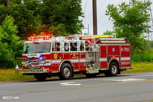 istock Sayreville NJ USA - Jujy 02, 2018: Firetruck driving on a road flashing blue lights a accident damaged car 992221450