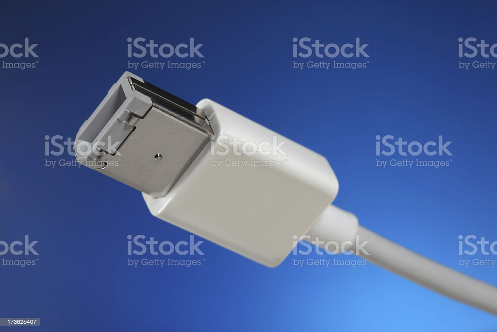 FireWire Cable Close-up of FireWire (IEEE 1394) connector (alpha plug / male) and cable on blue background. Blue Stock Photo