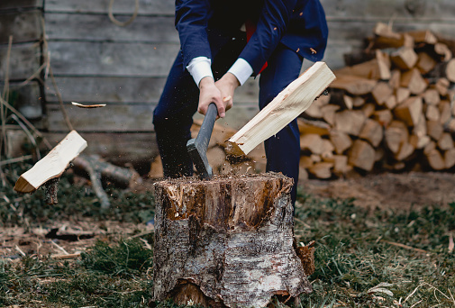 firewood and an axe. A man in a jacket chopping wood. Businessman on holiday in nature.