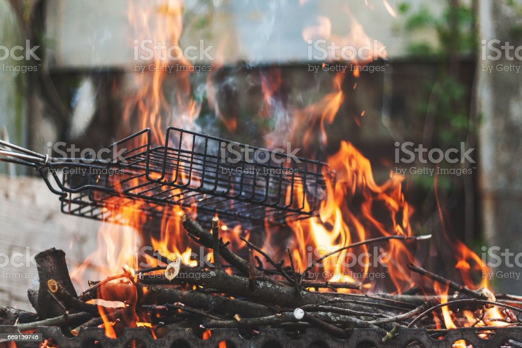 Firewood and branches for coals burn out in the brazier. Retro vintage effect. Keep the grill grate over the fire stock photo