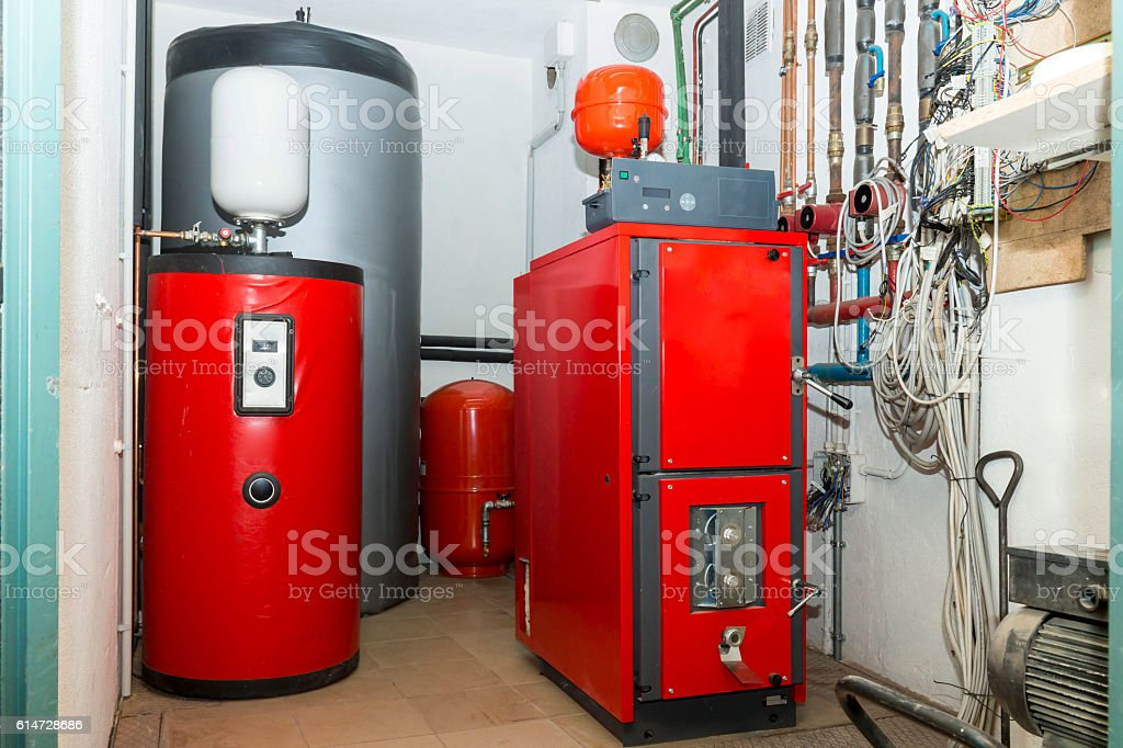 Firewood boiler and puffer thank in the boiler room stock photo