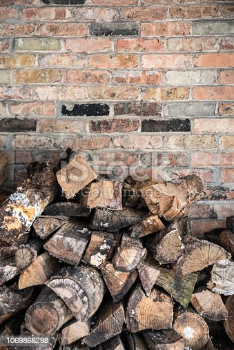 firewood cut and piled up on a heap against a brick wall