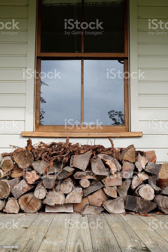 Firewood stacked under window stock photo