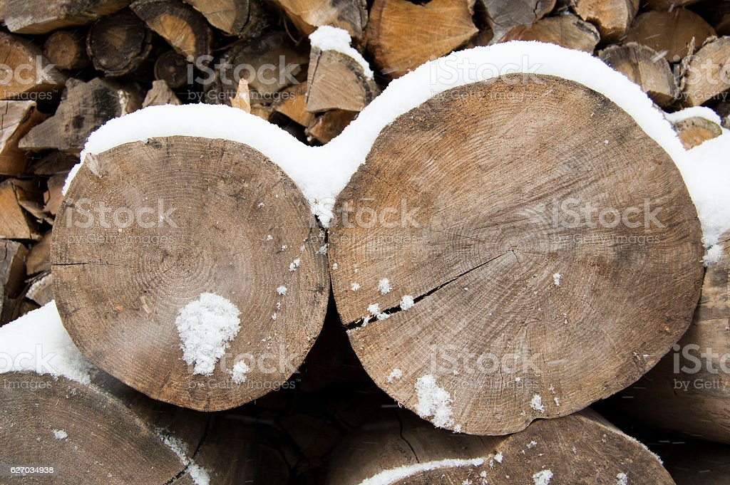 Firewoods, log pieces stored under snow in winter stock photo