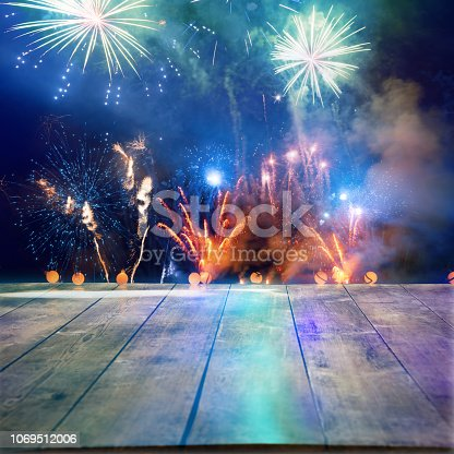 istock Firework Display Behind Wooden Floor For Celebration Events 1069512006