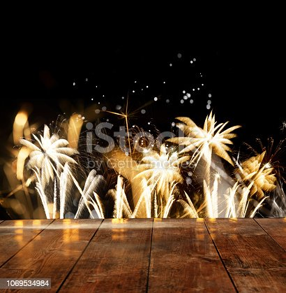 969086552istockphoto Firework Display Behind Wooden Floor For Celebration Events 1069534984