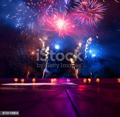 istock Firework display behind wooden table 875419904
