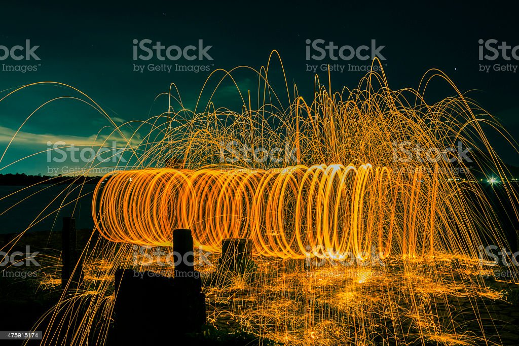 Firework showers of hot glowing sparks from spinning steel wool on...