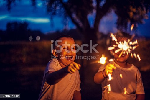 Boys have fun in the park with firework sparkles