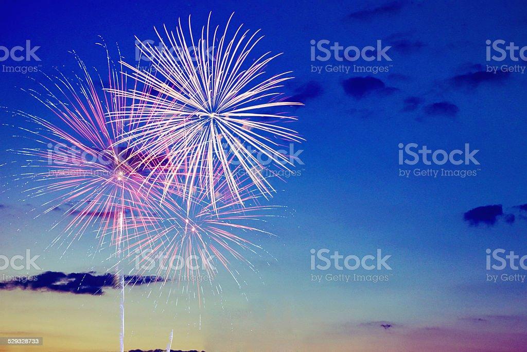 Fireworks against sunset stock photo