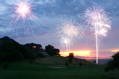 Fireworks celebration over a golf course on July 4th, independence Day, against a beautiful sunset.
