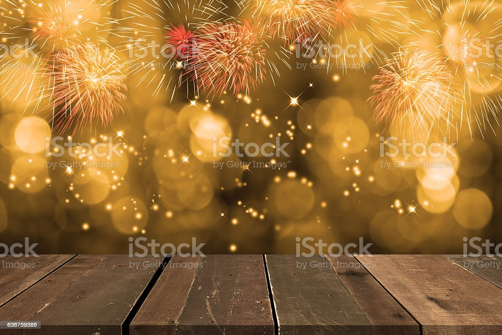 Fireworks blowing up with bokeh behind empty wooden table. stock photo