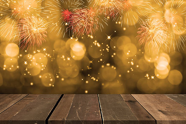 Fireworks blowing up with bokeh behind empty wooden table. - foto stock
