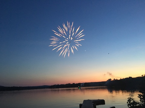 Fireworks by the lake at sunset on July 4th