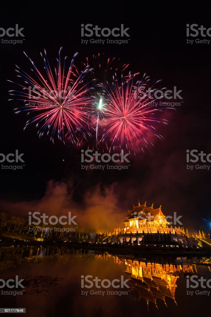 Fireworks celebrate the New Year 2018 at Rajapruek Royal Park, Chiang Mai with beutiful light of Hor Khum Luang temple,Thai Tradition Building. stock photo