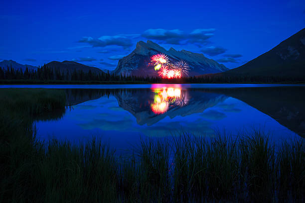 Fireworks in Banff This picture was taken in the Vermilion Lake on the Canada Day. We watched a beautiful fireworks show at the lake side.  canada day photos stock pictures, royalty-free photos & images
