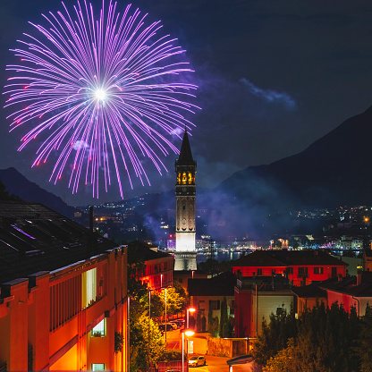 Bell tower view and fireworks in the city of Lecco, Lombardy, Italy.