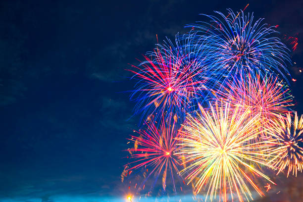 Fireworks of various colors bursting against a black stock photo