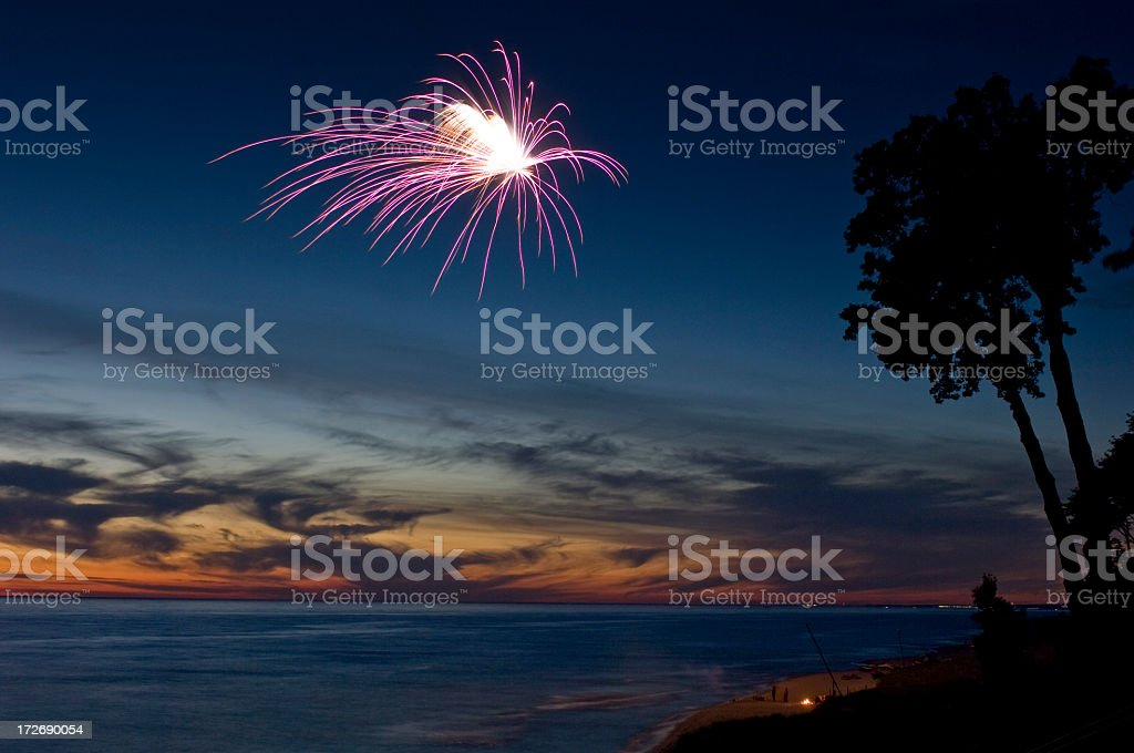 Fireworks on a beach at sunset stock photo