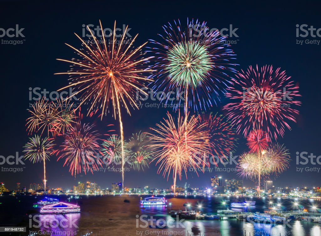 Fireworks over big city by the beach and sea surrounding with hotels, restaurant, and service boats and cruises during blue twilight for celebrating New Year eve and special occasion on holidays stock photo