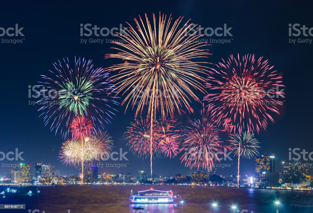 Fireworks over cityscape by the beach and sea surrounding with hotels, restaurant, and service boats and cruises during blue twilight for celebrating New Year eve and special occasion on holidays stock photo
