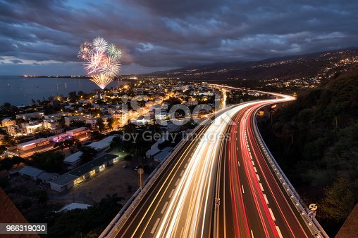 Amazing fireworks over light trails of cars on the tamarin road in Saint Paul, Reunion Island