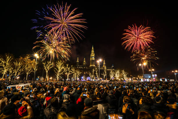 fireworks over Vienna people celebrating new year many people, locals and tourists, celebrating new years eve together with beautiful fireworks over city hall of Vienna pyrotechnic effects stock pictures, royalty-free photos & images