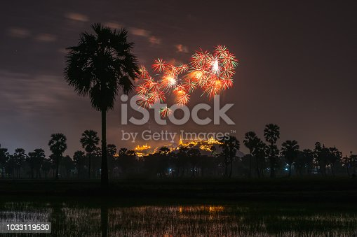 Beautiful colorful fireworks show at Phra Nakhon Khiri or (Khao Wang) with forground sugar palm, Petchaburi,Thailand