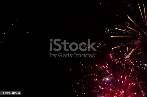 Red and orange fireworks placed in the corner of composition with big black copy space