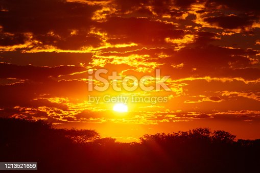 This is a color photograph of a vibrant orange and red cloudscape at sunset in Etosha National Park in Namibia, Africa.