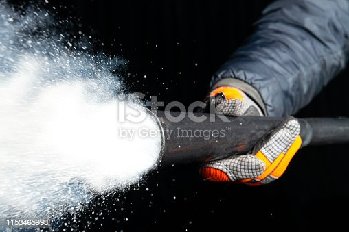 A man wearing safety gloves as he fires a CO2 extinguisher, with a cloud of carbon dioxide spraying from the nozzle.