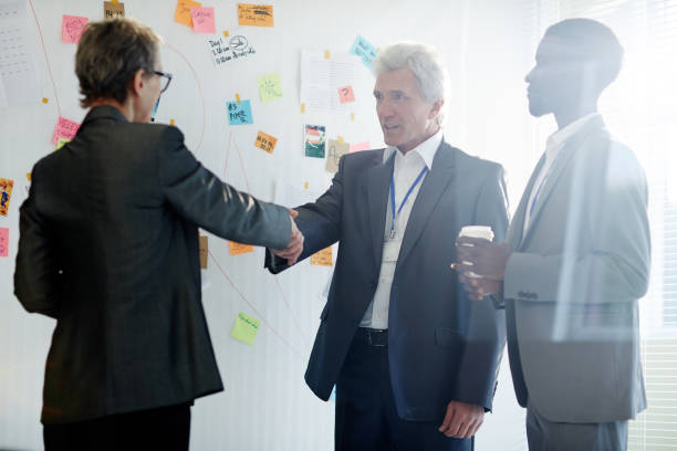 Firm Handshake of Business Partners Handsome senior entrepreneur wearing classical suit shaking hand of his female business partner after successful completion of negotiations, African American assistant manager standing next to them police meeting stock pictures, royalty-free photos & images