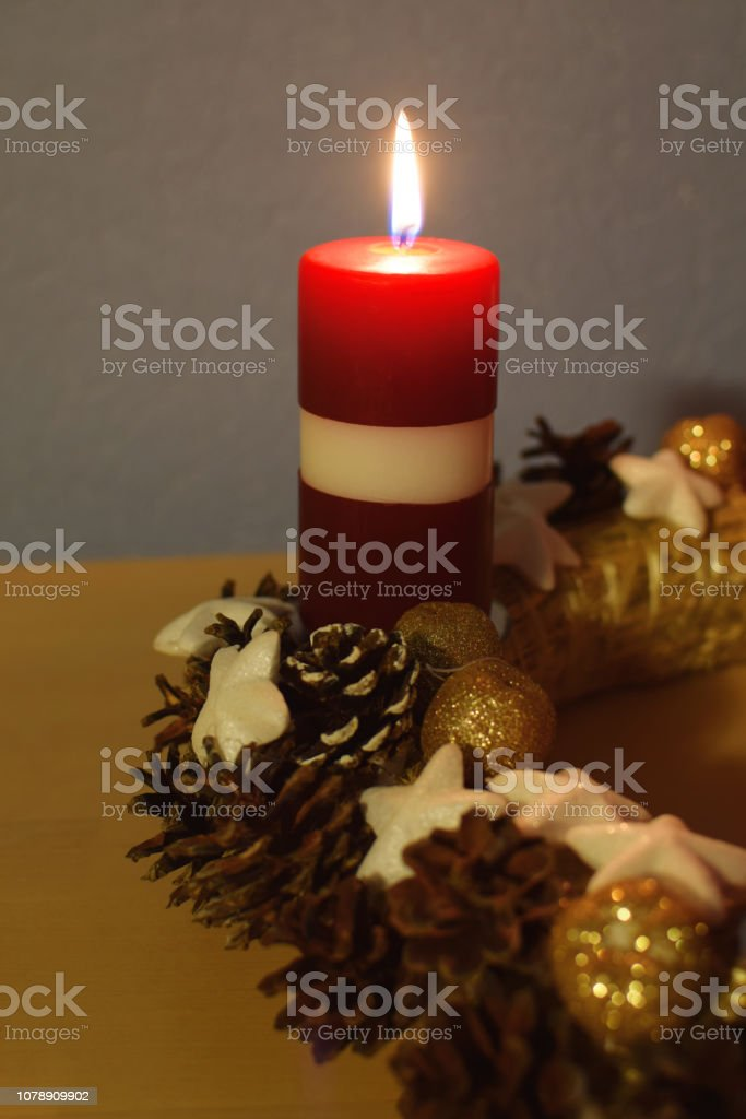 Red first advent candle burning with traditional christmas decoration...