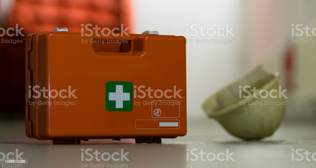 First aid after an accident at work. First aid kit and helmet near...