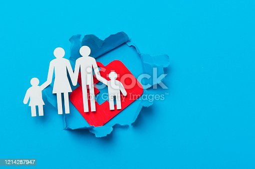 istock First aid bag sign and family in paper cut hole. Blue background 1214287947