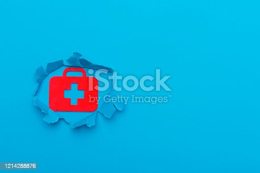 istock First aid bag sign in paper cut hole. Blue background 1214288876