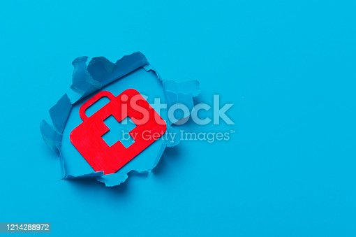 istock First aid bag sign in paper cut hole. Blue background 1214288972