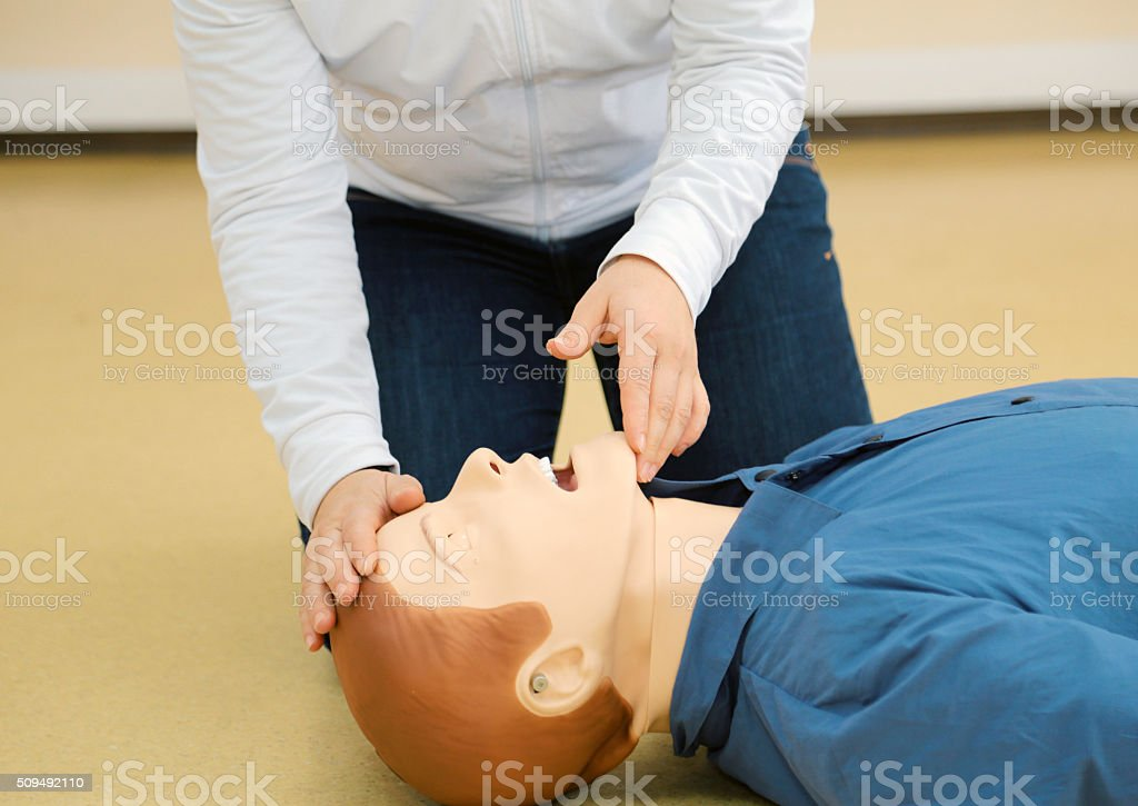 Woman performing first aid on a cpr dummy close up - pull up the chin.