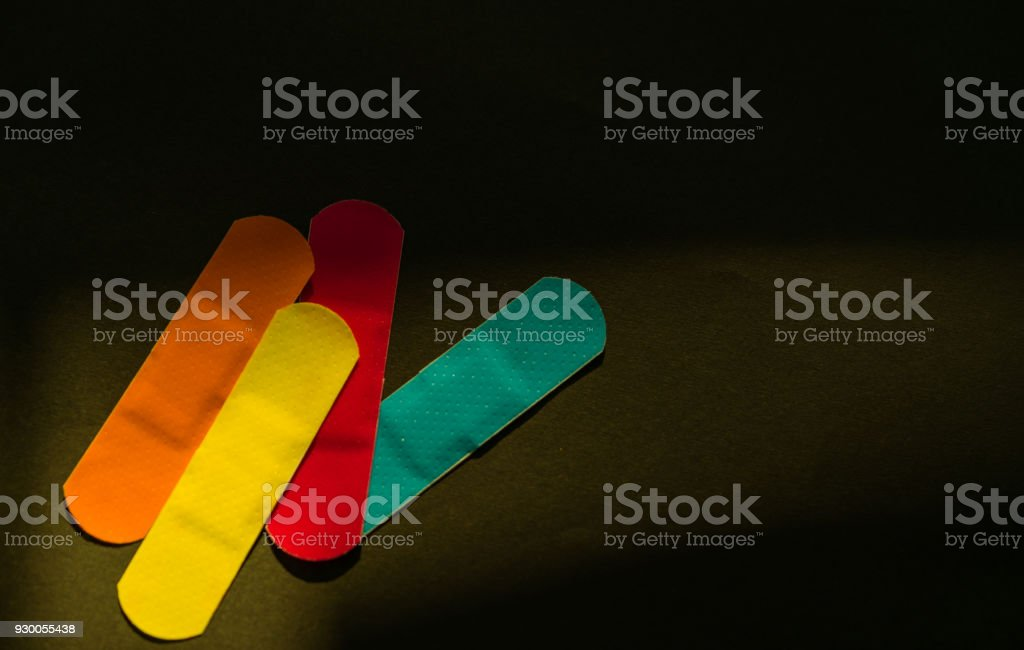 First aid dressing with non-stick pad for quick wound healing on dark background with copy space for text. Sterile wound dressing with bright color is easy to detect in food manufacturing industry stock photo
