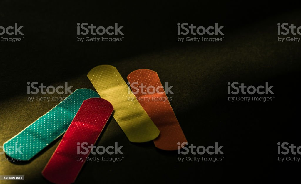 First aid dressing (Plaster) with non-stick pad for quick wound healing on dark background with copy space. Sterile wound dressing with bright color is easy to detect in food manufacturing industry stock photo