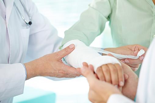 Doctor and nurse bandaging patient's broken arm