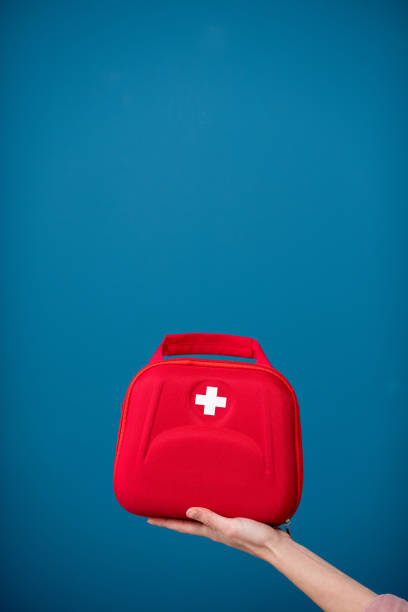 first aid kit on the blue background - first aid stock photos and pictures