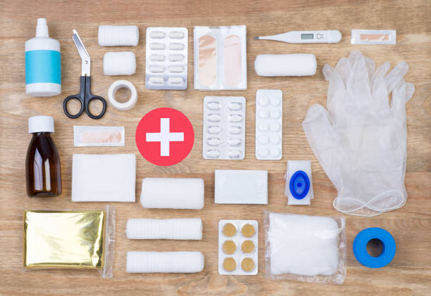 first aid kit on wooden background - first aid stock photos and pictures